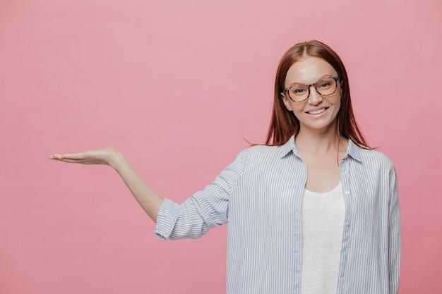 Mulher sorridente jovem positiva levanta a mão, finge segurando algo