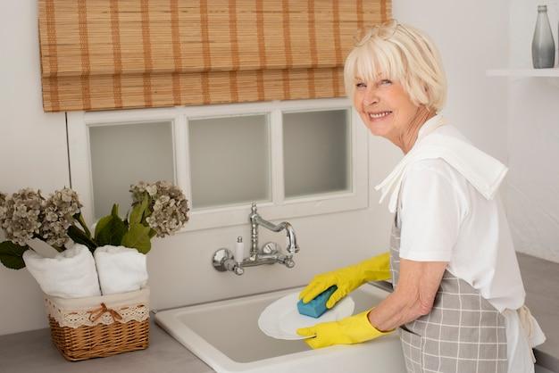 Mulher sorridente lavando os pratos com luvas