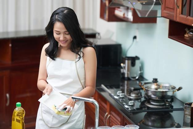 Mulher sorridente, lavando pratos