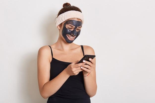 Mulher sorridente lendo mensagem no telefone inteligente com máscara preta no rosto, usando faixa de cabelo e camiseta sem mangas