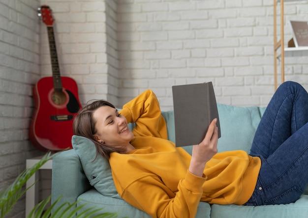 Mulher sorridente lendo no sofá