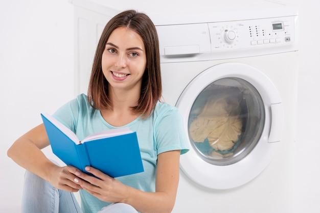 Mulher sorridente, lendo perto de máquina de lavar roupa