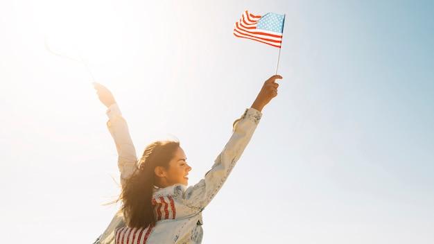 Mulher sorridente, levantando as mãos com a bandeira do eua