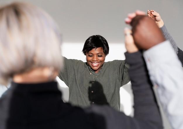 Mulher sorridente, levantando as mãos com as amigas