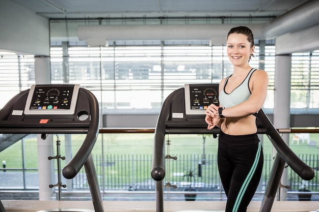 Mulher sorridente, ligado, treadmill, usando, esperto, relógio, em, ginásio