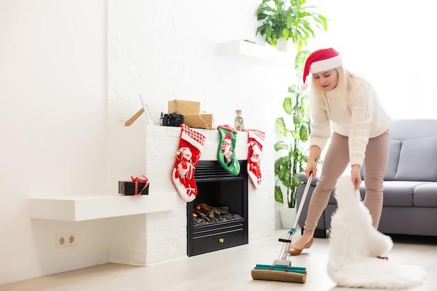 Mulher sorridente limpando a casa antes do natal