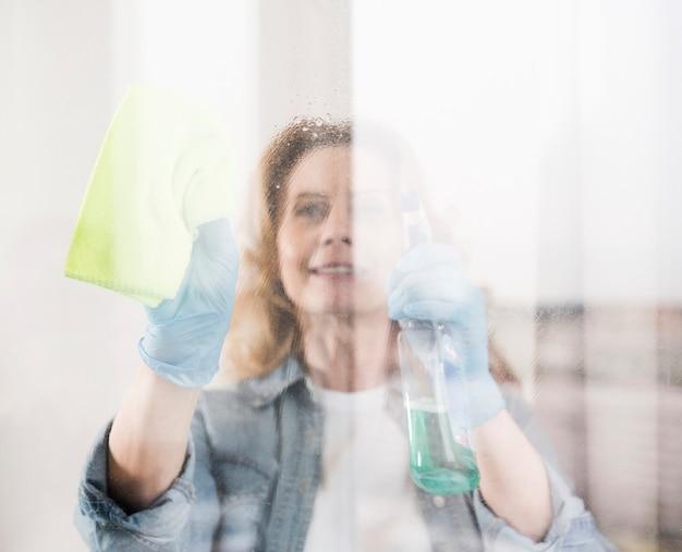 Mulher sorridente, limpando a janela com pano