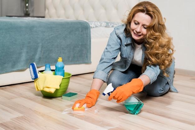 Mulher sorridente, limpando o chão