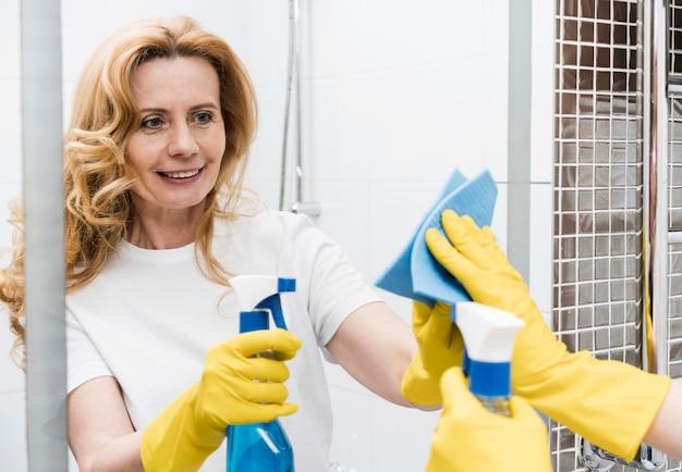 Mulher sorridente, limpando o espelho do banheiro