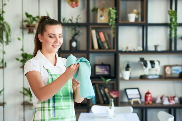 Mulher sorridente, limpando, vidro, de, cafeteria