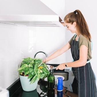Mulher sorridente, limpeza, utensílio, cozinha