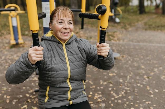 Mulher sorridente mais velha malhando ao ar livre