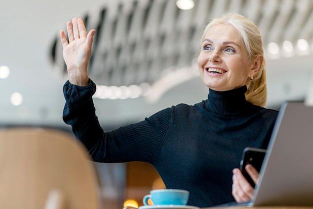 Mulher sorridente mais velha pedindo a conta enquanto trabalhava e tomava café