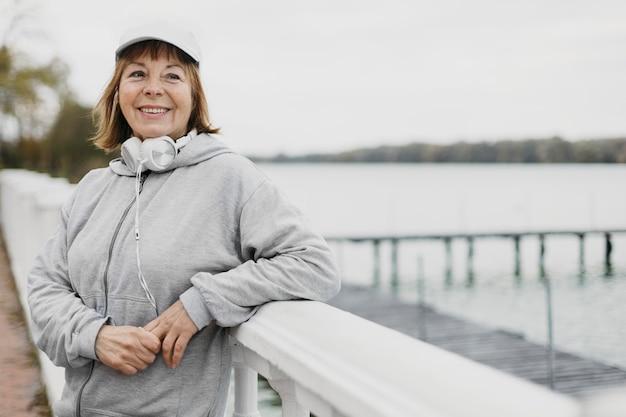 Mulher sorridente mais velha posando ao ar livre com fones de ouvido enquanto se exercita