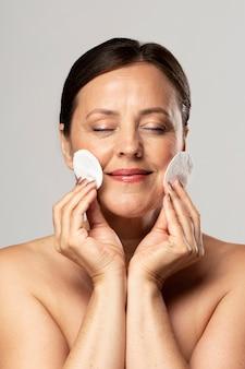 Mulher sorridente mais velha posando com almofadas de algodão para remoção de maquiagem