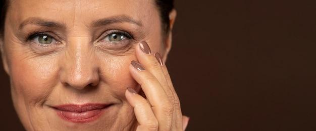 Mulher sorridente mais velha posando maquiada