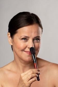 Mulher sorridente mais velha usando pincel de maquiagem no rosto
