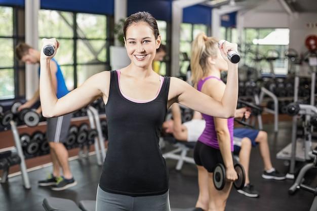 Mulher sorridente malhar com halteres no ginásio