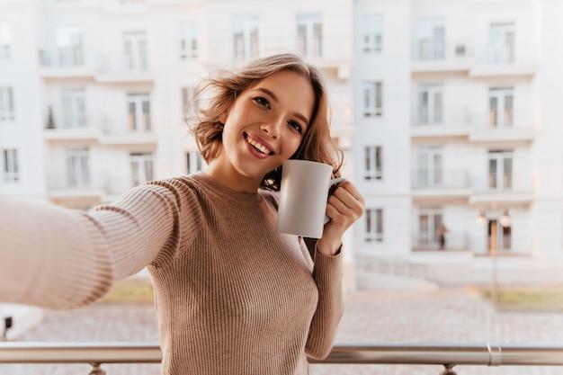 Mulher sorridente maravilhosa com uma xícara de café em pé na cidade. menina morena positiva, aproveitando a manhã com chá.