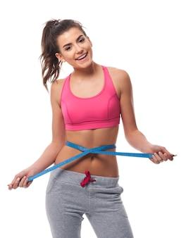 Mulher sorridente medindo a cintura com fita métrica