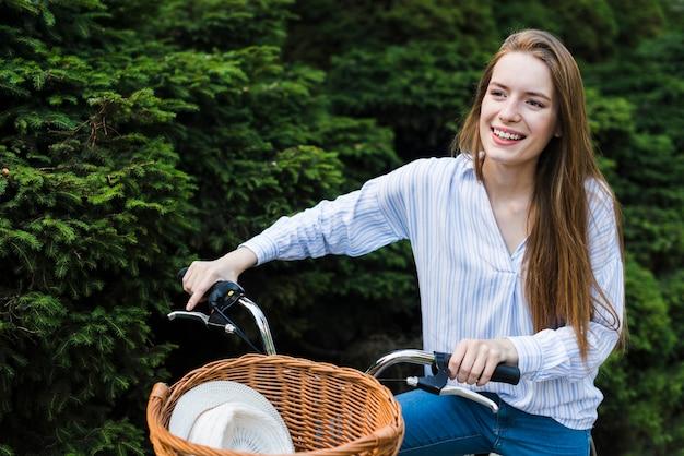 Mulher sorridente, montando uma bicicleta