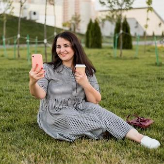 Mulher sorridente morena fazendo uma selfie enquanto segura o telefone