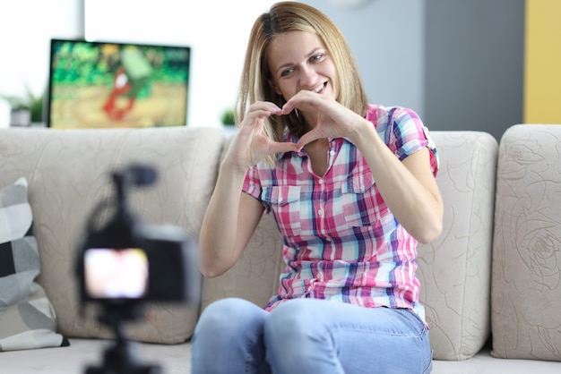Mulher sorridente mostra seu coração para a câmera no tripé