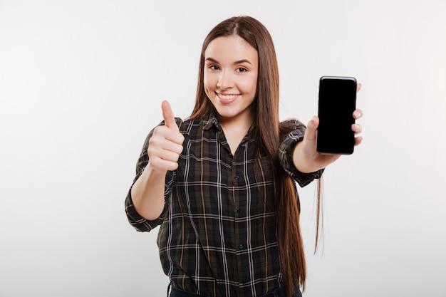 Mulher sorridente, mostrando a tela do smartphone em branco