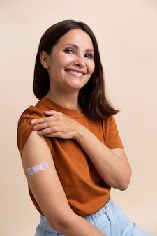 Mulher sorridente mostrando adesivo no braço após tomar vacina