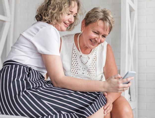 Mulher sorridente, mostrando, algo, de, cellphone, para, dela, mãe