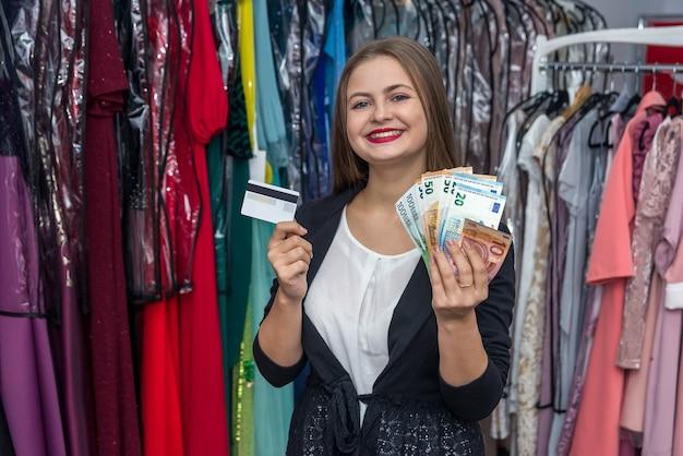 Mulher sorridente mostrando cartão de crédito e notas de euro Foto Premium