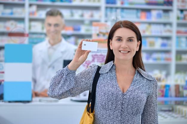 Mulher sorridente mostrando cartão de crédito na farmácia