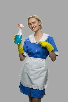 Mulher sorridente mostrando detergente para limpeza. empregada doméstica bonita oferecendo spray de limpeza em fundo cinza. serviço de limpeza da casa.