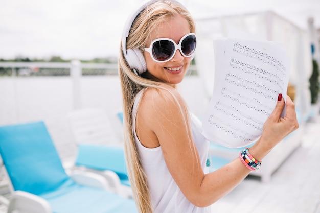 Mulher sorridente mostrando folhas de música