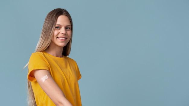 Mulher sorridente mostrando o braço com adesivo após tomar vacina