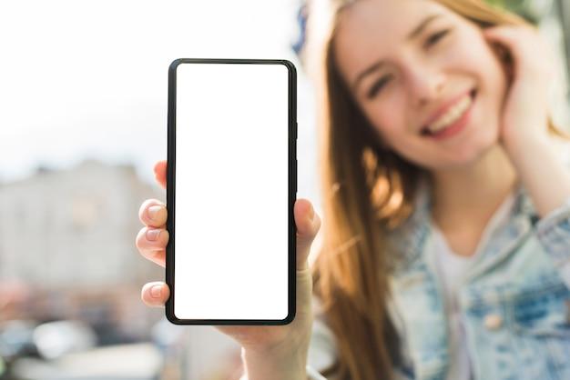 Mulher sorridente, mostrando o smartphone de tela em branco