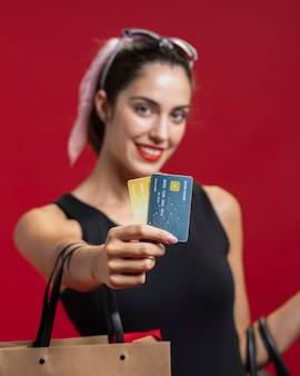Mulher sorridente, mostrando seus cartões de crédito