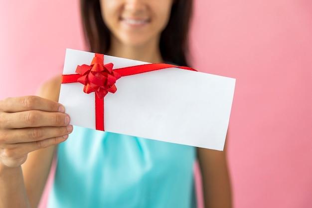 Mulher sorridente, mostrando um envelope