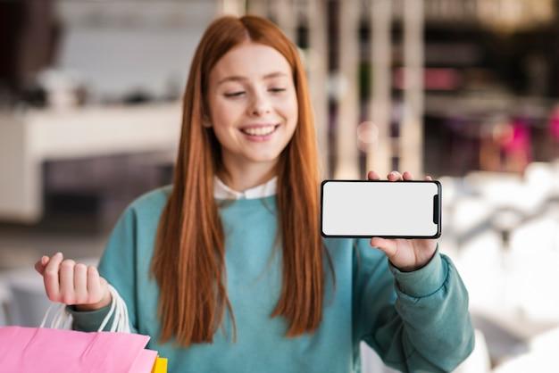 Mulher sorridente, mostrando um telefone simulado