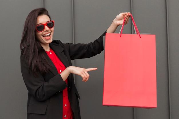 Mulher sorridente mostrando uma sacola de compras do espaço cópia vermelha