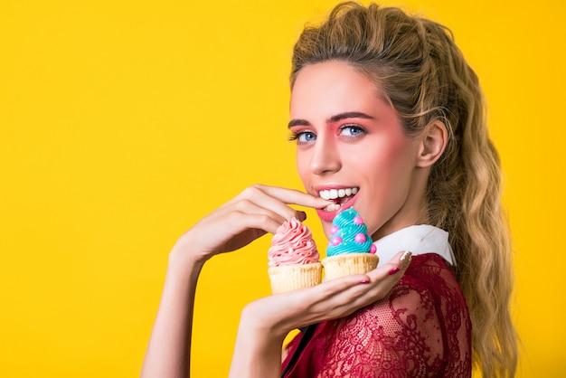 Mulher sorridente muito atraente está oferecendo dois bolinho saboroso.