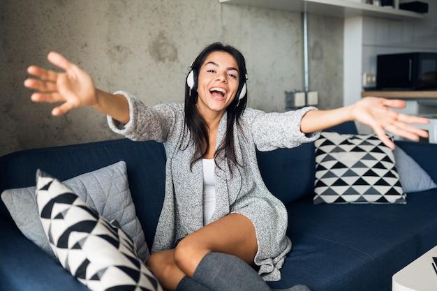 Mulher sorridente muito sexy em roupa casual sentada na sala de estar ouvindo música em fones de ouvido, se divertindo em casa