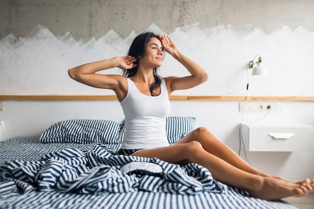 Mulher sorridente muito sexy sentada na cama pela manhã, acordar cedo, preguiçosa