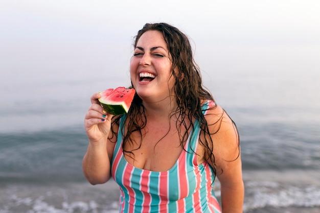 Mulher sorridente na água na praia comendo melancia