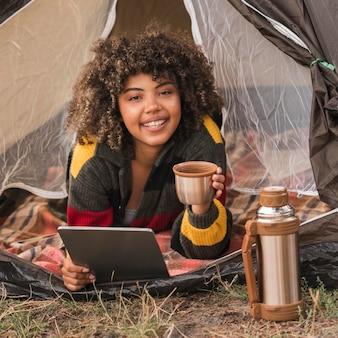 Mulher sorridente na barraca enquanto acampa segurando bebida e tablet