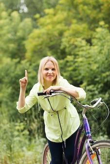 Mulher sorridente na bicicleta apontando para cima