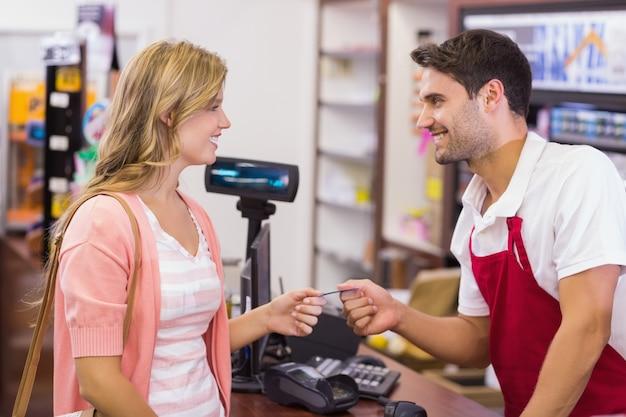 Mulher sorridente na caixa registradora que paga com cartão de crédito
