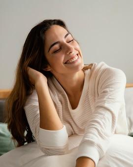 Mulher sorridente na cama em casa