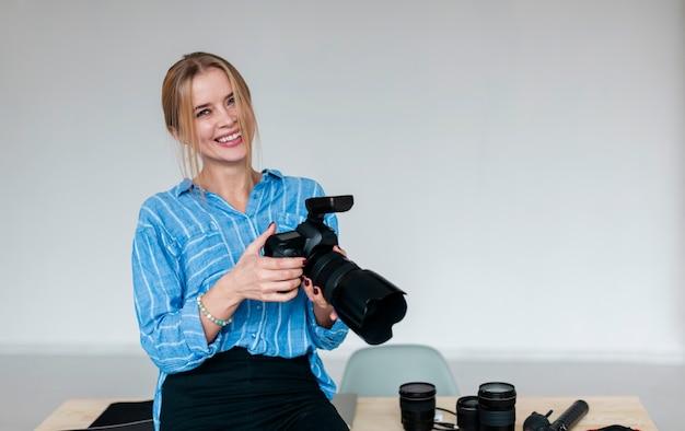 Mulher sorridente na camisa azul, segurando uma câmera