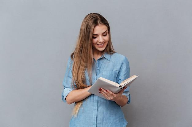 Mulher sorridente na camisa lendo livro